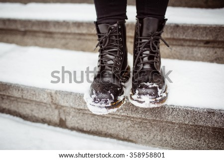 Black women's shoes on the stone steps covered by snow in the winter. #358958801