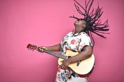 black womnlan playing a guitar passionately, rocking hard, throwing her hair