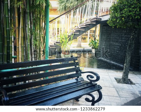 Black wood bench in a garden with a shady atmosphere, vintage style.