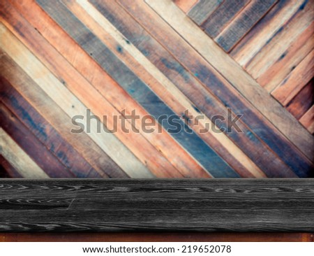 Black wood table at blurred colorful plank wooden wall in background,Template for display your product