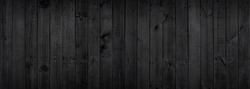 Black wood texture background coming from natural tree. The wooden panel has a beautiful dark pattern that is empty.