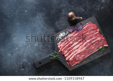 Black wooden chopping board with raw marbled beef bacon, horizontal shot with copyspace on a dark scratched metal background, top view