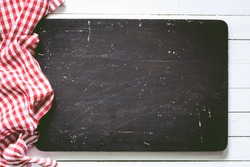 Black wooden cutting board and red plaid textile. Food background with copy space, Horizontal