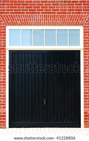 Black Wooden Garage Doors with a red brick surround