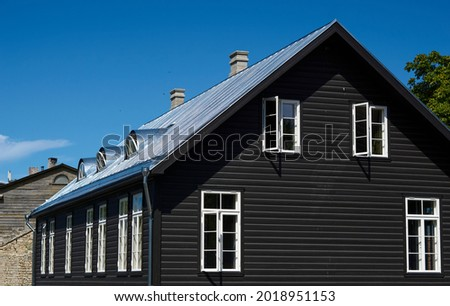 black wooden house under a gray roof against a blue sky. building architecture. High quality photo
