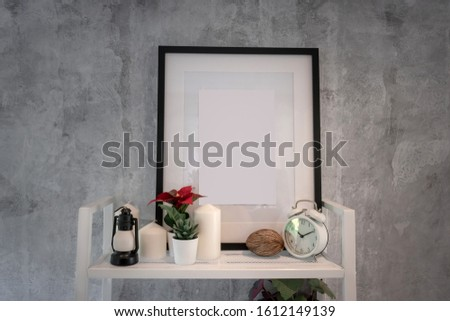 Black wooden picture frame with clock and candle light on the white shelf decoration