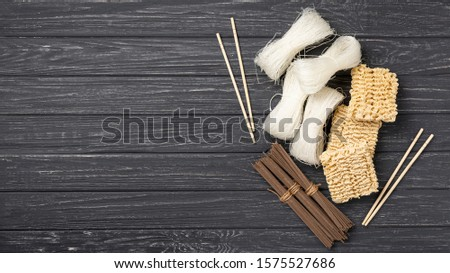 Black wooden table with uncooked noodles