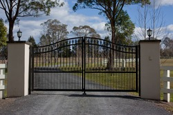 Black wrought iron entrance gates to rural property with trees and sky in background