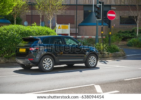 Black 4x4 car in the city centre on sunny day. #638094454