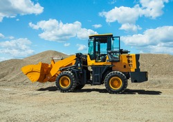 Black-yellow front loader with small wheels against the background of a large pile of stone sand and a blue sky with white clouds. Side view.