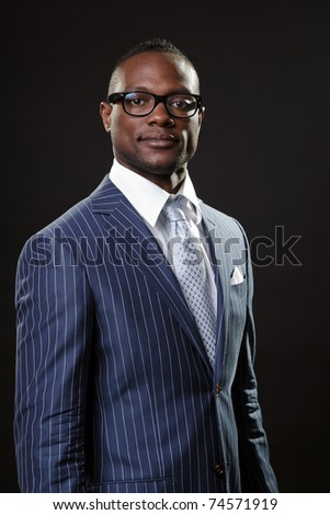 Black young business man in suit with glasses looking serious.