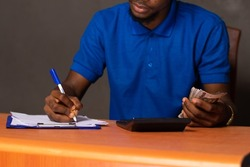 black young man doing some calculations, holding some money