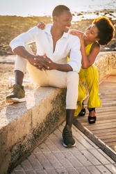 Black young people couple enjoy together leisure outdoor activity with beach and sunlight inbackground - concept of african man and woman in relationship or friendship