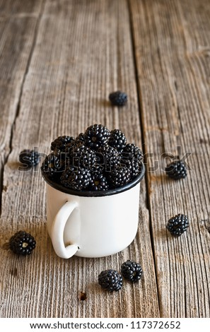 Blackberries in a white mug on wooden rustic table - stock photo