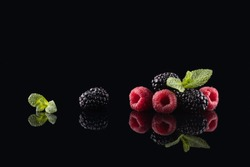 Blackberry and raspberry with mint leafs on the black glass background with a reflection