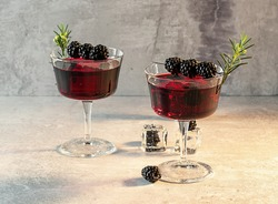 Blackberry Bramble with fresh muddled blackberries, gin, lemon juice, and soda water. Refreshing summer cocktail with ice.