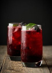 Blackberry cocktail with crushed ice on the rustic wooden background. Selective focus. Shallow depth of field.
