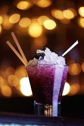 Blackberry cocktail with ice in a glass with a straw