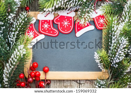 Blackboard blank framed in beautiful Christmas tree branches and decorations. Winter holidays concept. Copy space for your text