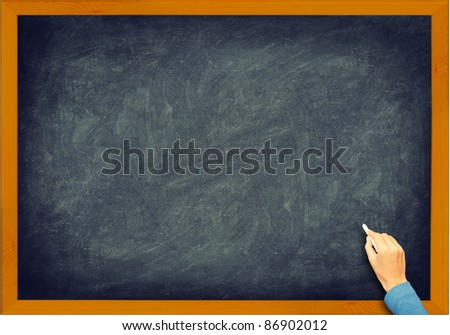 Blackboard closeup. Vintage retro chalkboard with hand, chalk and frame. Nice texture. - stock photo