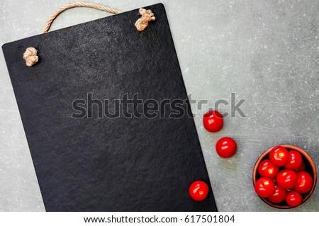 Blackboard for writing menu, recipe, fresh tomatoes chili. Close-up on top.