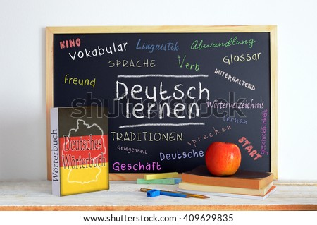 Blackboard in a German language classroom with the message LEARN GERMAN and some other linguistic words.