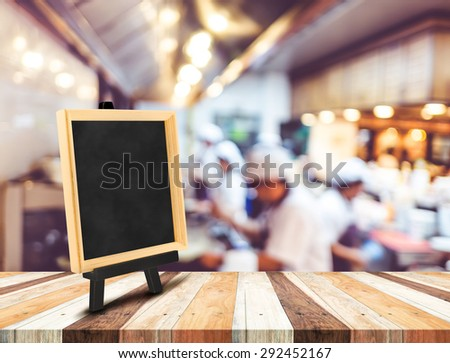 Blackboard menu with easel on wooden table with blur open kitchen at  restaurant background, Copy space for adding your content #292452167
