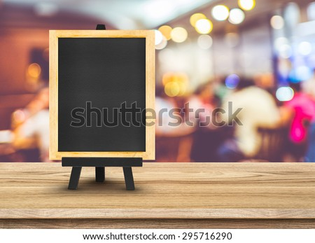Blackboard menu with easel on wooden table with blur restaurant background, Copy space for adding your content
