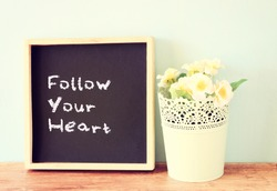blackboard over wooden shelf with the phrase follow your heart