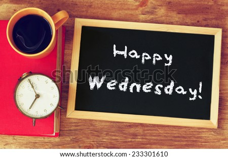 blackboard over wooden table with cup of coffee and and the phrase it's happy wednesday