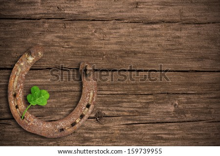 Blackboard with four-leaved clover and a horse shoe