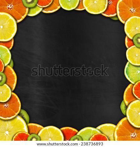 Blackboard with Fruit Frame. Frame of oranges, lemons and kiwi on an empty blackboard