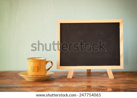 blackboard with room for text next to cup of coffee over wooden table, filtered image.