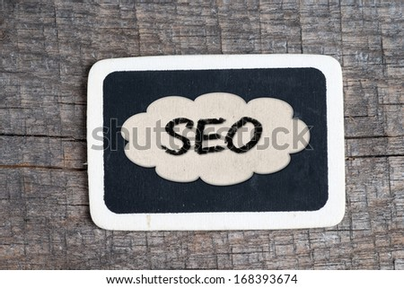 Blackboard with SEO Concept on wood background