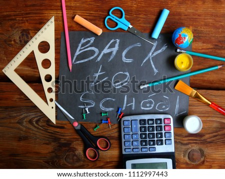 Blackboard with the Back to School text and school supplies around. Flat lay photo maded in school concept