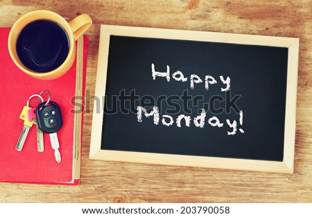blackboard with the phrase happy monday written on it, coffee cup and car keys. filtered image.