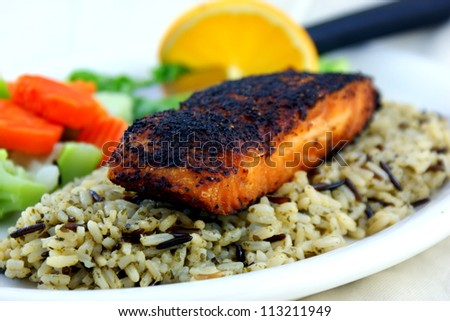 Blackened salmon served on wild rice with vegetables.