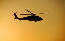 Blackhawk helicopter against a sunset sky