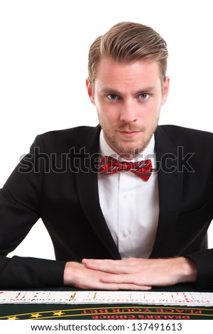 Blackjack dealer in a suit and bowtie with cards. White background.
