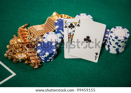 Blackjack 21 hand of a King and an Ace playing Cards on Casino green felt with chips and gold jewelry