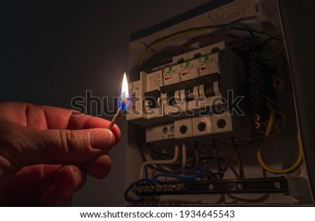 Blackout concept. Person's hand in complete darkness holding a burning match to investigate a home fuse box during a power outage.