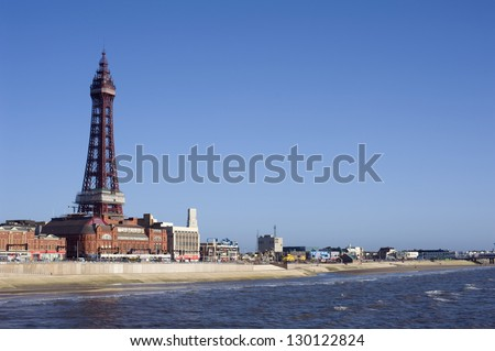 Blackpool waterfront and beach with Blackpool Tower, a historical Victorian lattice structure, overlooking the ocean