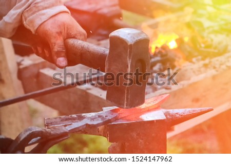 Blacksmith hammer hits the hot metal. Forging of iron objects in a retro forge. The process of working on the manufacture of weapons blacksmith on the anvil. stock photo