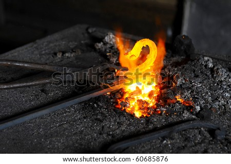 blacksmith heats a decorative piece in the forge
