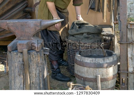 blacksmith in a medieval forge preparing to workblacksmith medieval blacksmith with an anvil, a barrel and a basket with coal