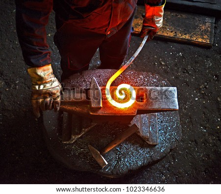 Blacksmith is processing a hot metal object of a spiral shape at anvil in a workshop