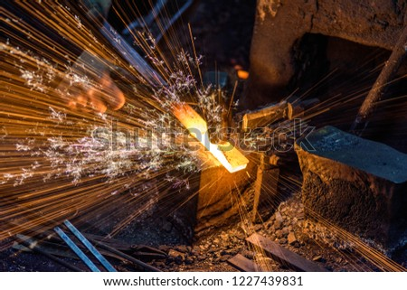 Blacksmith manually forging the molten metal on the anvil with spark fireworks #1227439831