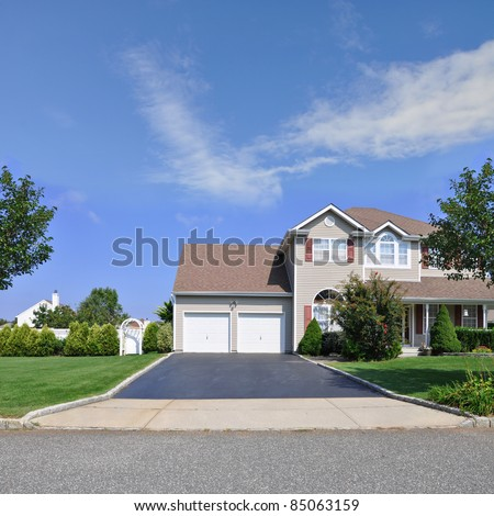 Blacktop Driveway of Split Level Suburban Home with Double Garage Door Two Story Residence in Residential Neighborhood