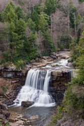 Blackwater falls in the early spring viewed from above with slight time lapse for blurred water flow. Water flows over rocks with pines on either side.