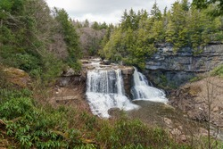 Blackwater falls in the early spring with pine trees and rhododendron growing over rocks